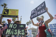 Demonstrators hold signs as they protest the lockdown and wearing masks Saturday, June 27, 2020, in Huntington Beach, Calif. (AP Photo/Marcio Jose Sanchez)