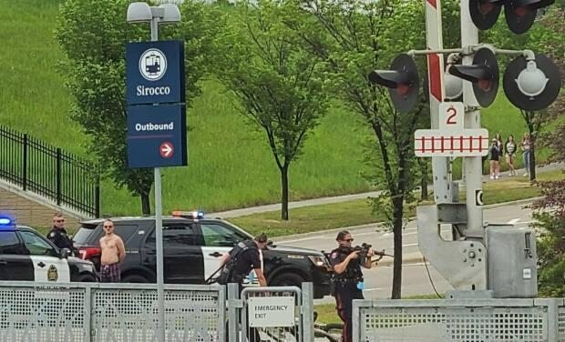 Police with guns drawn respond to an incident at Sirocco CTrain Station in southwest Calgary on Wednesday.  (Submitted by Mackenzie Sampson - image credit)