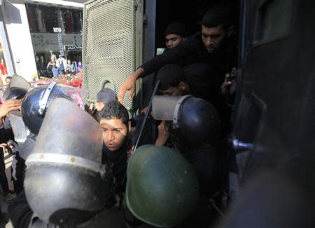Riot police detain a man, who was protesting against a new law restricting demonstrations, in downtown Cairo November 26, 2013. REUTERS/Amr Abdallah Dalsh