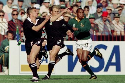 All Blacks Glen Osborne (L) and Jeff Wilson and Springbok Chester Williams seek possession during the 1995 Rugby World Cup final in Johannesburg