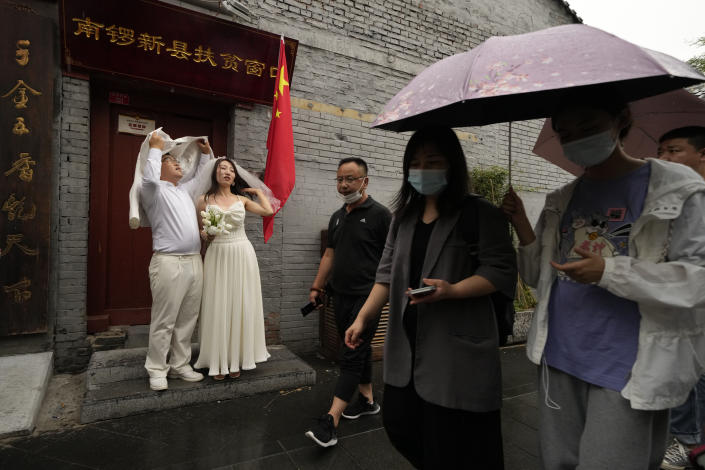 """A wedding couple takes shelter from the rain as visitors pass through the popular Nanluoguxiang alley way in Beijing on Saturday, July 3, 2021. A small but visible handful of urban Chinese are rattling the ruling Communist Party by choosing to """"lie flat,"""" or reject high-status careers, long work hours and expensive cities for a """"low-desire life."""" That clashes with party ambitions to make China a wealthier consumer society. (AP Photo/Ng Han Guan)"""