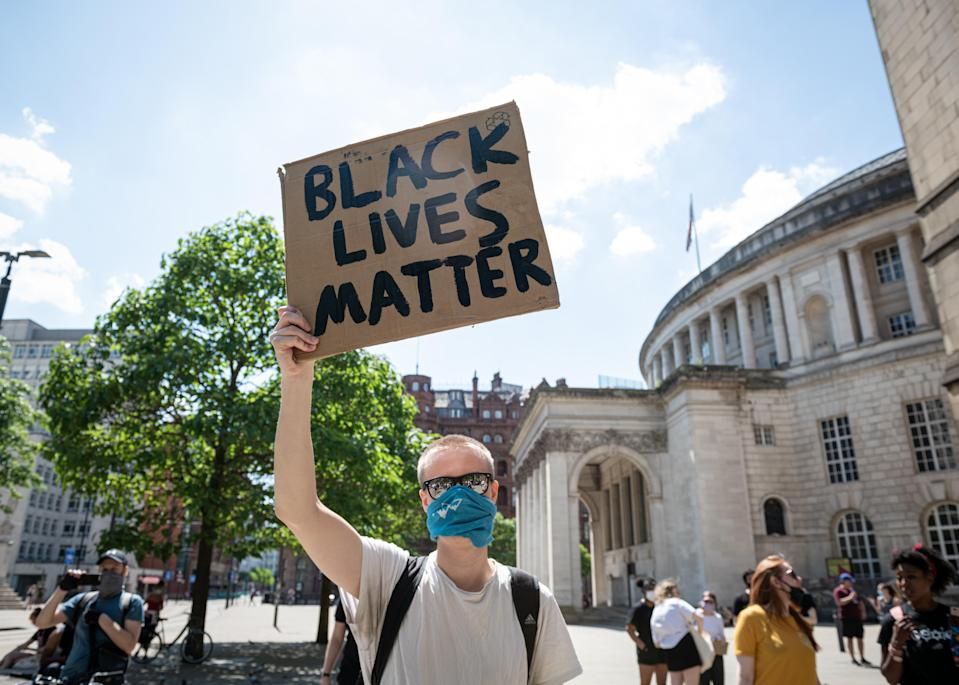 """A protester holds a """"Black Lives Matter"""" placard during a demonstration in Manchester city centre. (SOPA Images/Sipa USA)"""