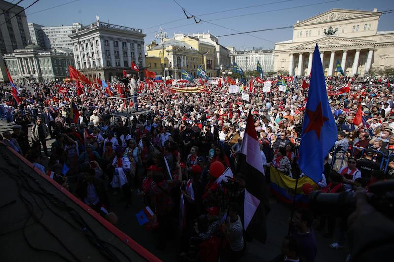 Thousands of Communists gather in downtown Moscow after the May Day march, Thursday, May, 1, 2014. About 100,000 people marched through Red Square to celebrate May Day, the first time the annual parade has been held on the vast cobblestoned square outside the Kremlin since the fall of the Soviet Union in 1991. The Bolshoi Theater is at the background, right. (AP Photo/Denis Tyrin)
