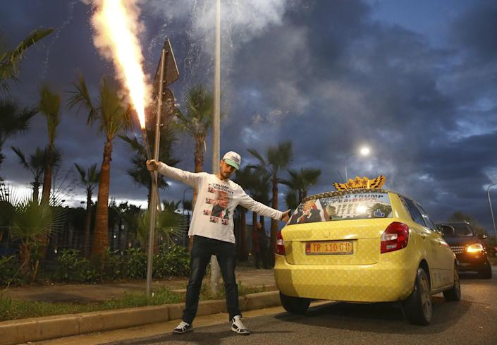 """<p>Albanian taxi driver Uljan Kolgjegja lights fireworks to celebrate after Donald Trump was named as US President-elect, in Tirana, Wednesday, Nov. 9, 2016. Kolgjegja has plastered his cab with Trump's pictures, which he says has helped his business prosper. He was prompted to decorate his taxi with pictures of the Republican candidate after Albania's Prime Minister Edi Rama said Trump could be """"a real threat to Albanian-American ties."""" (AP Photo/Hektor Pustina) </p>"""