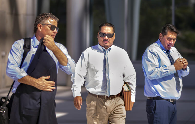 Lawyer Mark Fleming, left, walks with defendant Albert Lopez past defendant Bradley Campos outside the Lloyd George U.S. Courthouse Thursday, Feb. 6, 2020, following opening statements in a federal racketeering trial for eight Vagos Motorcycle Club members on Aug. 12, 2019, in Las Vegas. (L.E. Baskow/Las Vegas Review-Journal via AP)