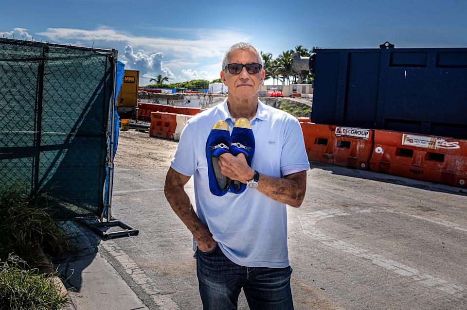 Former Champlain South resident Steve Rosenthal stands at 88th St. and Collins Ave. in Surfside, Florida, with the gold tip shoes he saved when he was rescued on the night the building collapsed.