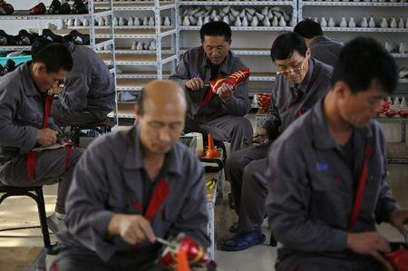 FILE PHOTO - North Korean workers make soccer shoes inside a temporary factory at a rural village on the edge of Dandong