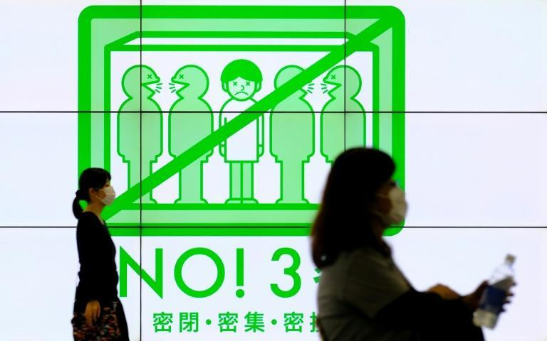 Signs promote social distancing in Tokyo's Shinjuku district as the country battles another uptick in Covid-19 infections