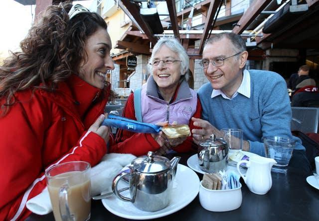 Great Britain's Amy Williams, left, shows her gold medal to her mum Jan and dad Ian