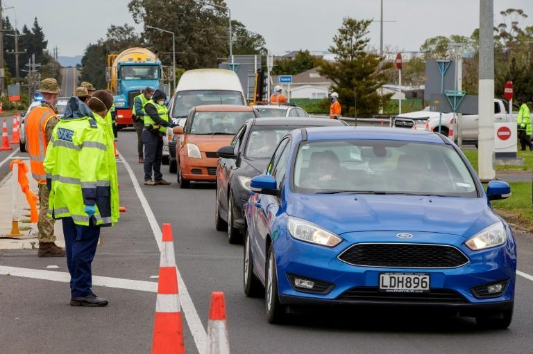 Police and military personnel check vehicles leaving Auckland as New Zealand rushes to track the source of a sudden return of the coronavirus
