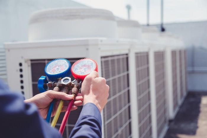 An HVAC technician checking readings on a commercial air conditioning system.