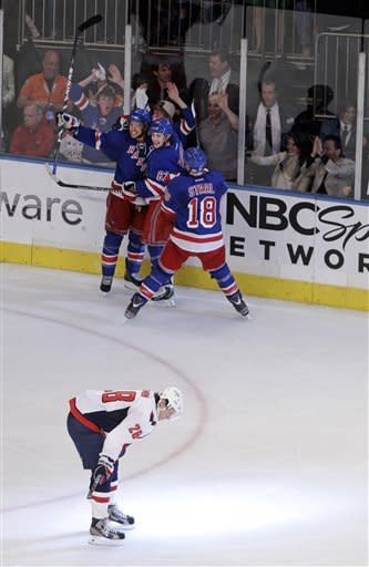 Washington Capitals left wing Alexander Semin (28) reacts as New York Rangers' Michael Del Zotto, upper left, celebrates with teammates Carl Hagelin (62) and Marc Staal (18) after scoring a goal during the third period of Game 7 of a second-round NHL hockey Stanley Cup playoff series on Saturday, May 12, 2012, in New York. (AP Photo/Frank Franklin II)