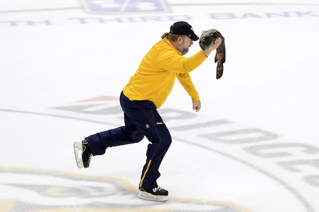 "A <a class=""link rapid-noclick-resp"" href=""/nhl/teams/nas/"" data-ylk=""slk:Nashville Predators"">Nashville Predators</a> crew employee skates off the ice carrying a catfish before the start of Game 3 between the <a class=""link rapid-noclick-resp"" href=""/nhl/teams/ana/"" data-ylk=""slk:Anaheim Ducks"">Anaheim Ducks</a> and the Nashville Predators in an NHL hockey first-round Stanley Cup playoff series Tuesday, April 19, 2016, in Nashville, Tenn. (AP Photo/Mark Zaleski)"