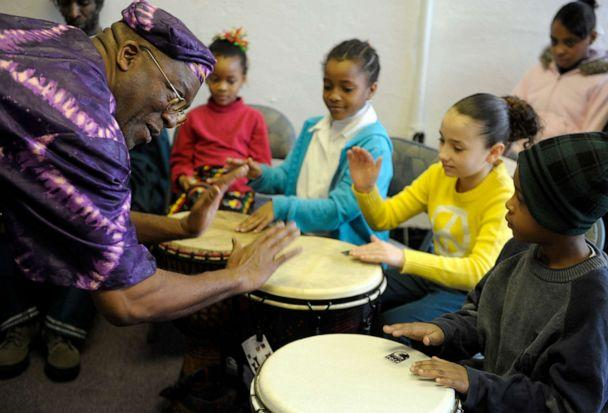 PHOTO: Dwight Baldwin gives African drumming pointers to children during Kwanzaa observances at Kente Cultural Center in New London, Conn., Dec. 27, 2012. (Sean D. Elliot/The Day via AP, FILE)