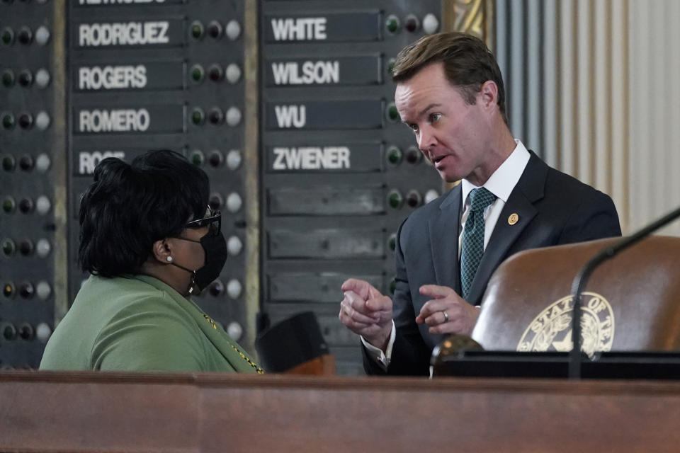 Speaker of the House Dade Phelan, R-Orange, right, talks with Rep. Toni Rose, D-Balch Springs, as the House debates election bill SB1, Thursday, Aug. 26, 2021, in Austin, Texas. (AP Photo/Eric Gay)