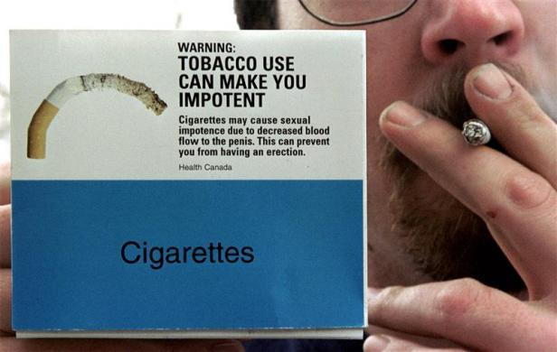 A smoker poses with a mock-up of packaging for cigarette packs in Canada.