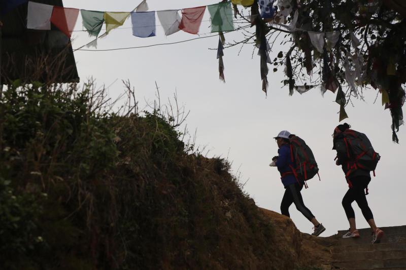 In this photo taken Saturday, March 30, 2019, Nima Doma, 34, right, and Furdiki Sherpa, 43, perform morning exercises as they train to summit Mount Everest, in Kathmandu, Nepal. Five years after one of the deadliest disasters on Mount Everest, three people from Nepal's ethnic Sherpa community, including Doma and Sherpa, are preparing an ascent to raise awareness about the Nepalese mountain guides who make it possible for hundreds of foreign climbers to scale the mountain and survive. The two women lost their husbands in the 2014 ice avalanche on Everest's western shoulder that killed 16 fellow Sherpa guides. (AP Photo/Niranjan Shrestha)