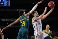 Italy's Achille Polonara (33) drives to the basket past Australia's Matisse Thybulle (10) during a men's basketball preliminary round game at the 2020 Summer Olympics, Wednesday, July 28, 2021, in Saitama, Japan. (AP Photo/Charlie Neibergall)