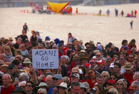 Surf lifesavers can be seen behind protesters participating in a national Day of Action against the Indian mining company Adani's planned coal mine project in north-east Australia, at Sydney's Bondi Beach in Australia, October 7, 2017.      REUTERS/David Gray
