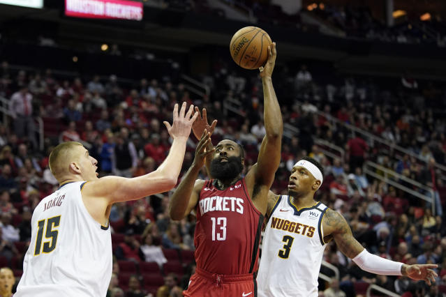 Houston Rockets' James Harden (13) shoots as Denver Nuggets' Nikola Jokic (15) and Torrey Craig (3) defend during the second half of an NBA basketball game Wednesday, Jan. 22, 2020, in Houston. The Rockets won 121-105. (AP Photo/David J. Phillip)