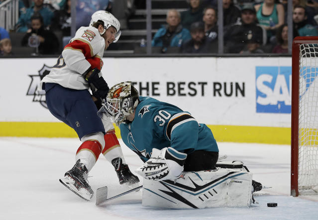 Florida Panthers' Mike Hoffman, left, scores a goal against San Jose Sharks' Aaron Dell (30) during the second period of an NHL hockey game Monday, Feb. 17, 2020, in San Jose, Calif. (AP Photo/Ben Margot)