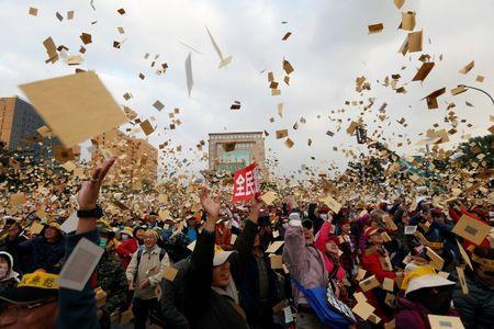Protesters throw hell money during a rally against the overhaul of the military and civil service pension fund, outside the Presidential Office in Taipei,Taiwan January 22, 2017. REUTERS/Tyrone Siu