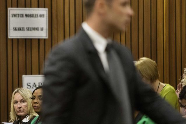 Reeva Steeenkamp's mother June (back L) looks on as Olympic and Paralympic track star Oscar Pistorius stands in the dock during court proceedings at the North Gauteng High Court in Pretoria March 18, 2014. Pistorius is on trial for murdering his girlfriend Steenkamp at his suburban Pretoria home on Valentine's Day last year. REUTERS/Marco Longari/Pool (SOUTH AFRICA - Tags: SPORT ATHLETICS CRIME LAW)