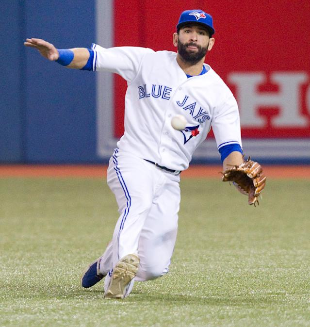 Toronto Blue Jays' Jose Bautista slides to get a sinking fly ball off the bat of Kansas City Royals' Omar Infante during tje seventh inning of a baseball game in Toronto on Friday, May 30, 2014. Infante was out at first. (AP Photo/The Canadian Press, Fred Thornhill)