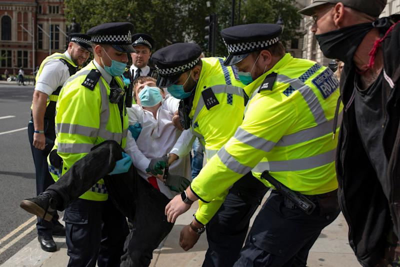 Police try to carry away an Extinction Rebellion protester who has 'gone floppy' at the point of arrest in Parliament Square.