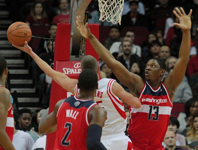 Washington Wizards center Kevin Serphin (13) defends as Houston Rockets forward Chandler Parsons, center, goes up to shoot and Wizards' John Wall looks on during the first half of an NBA basketball game in Houston, Wednesday, Feb. 12, 2014. (AP Photo/Richard Carson)