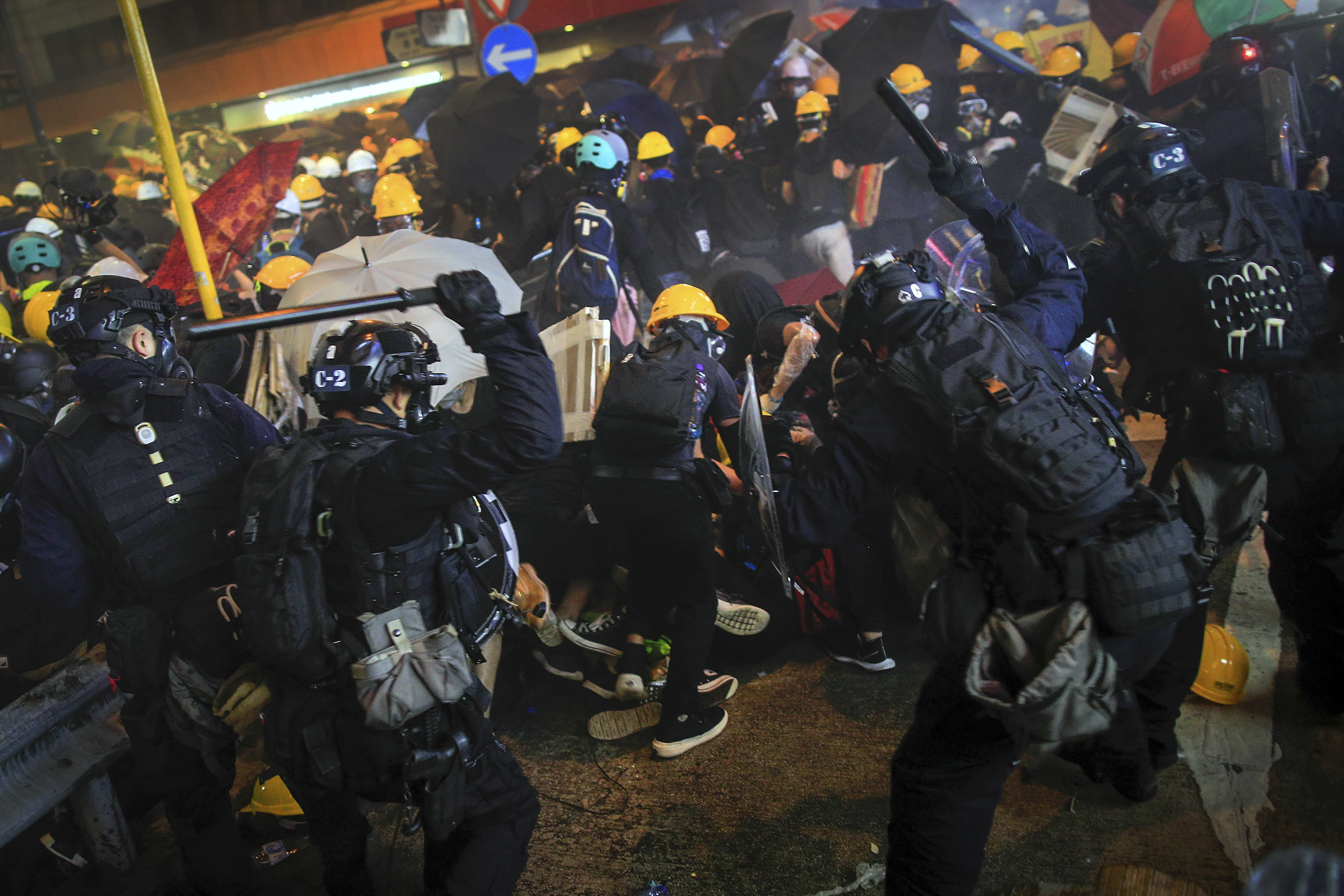 Policemen use batons charge on protesters during a protest in Hong Kong, Sunday, July 28, 2019. Police fired tear gas at protesters in Hong Kong on Sunday for the second night in a row in another escalation of weeks-long pro-democracy protests in the semi-autonomous Chinese territory. (Jeff Cheng/HK01 via AP)