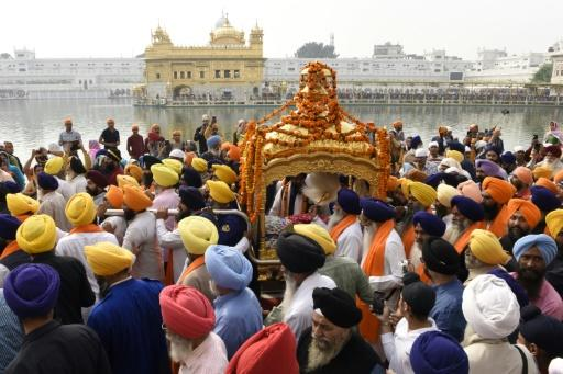 Devotees carry the Sikh holy book during a procession in Amritsar