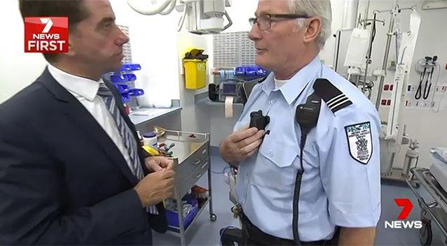 Security chief Graham Bushell shows Health Minister Cameron Dick how the simple cameras work. Source: 7 News