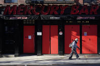 FILE - In this Jan. 10, 2021, file photo, a pedestrian walks past a boarded-up bar in the Hell's Kitchen neighborhood of New York. The boarded-up windows and For Rent signs are all over the place in Manhattan's Hell's Kitchen neighborhood. (AP Photo/Mary Altaffer, File)