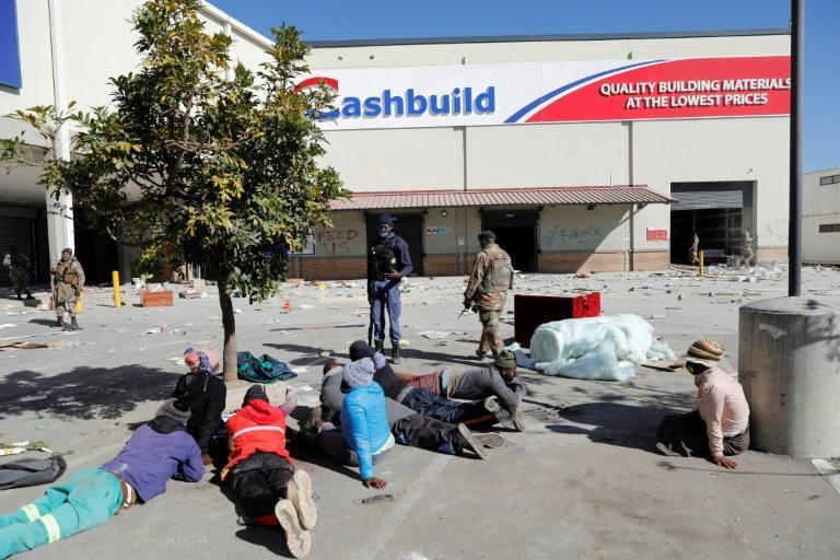 South African troops patrol the ransacked Diepkloof Square shopping mall in Soweto as suspected looters lie on the ground