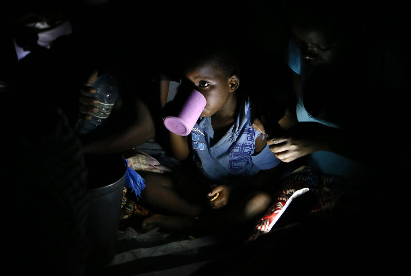 Displaced children, victims of Cyclone Idai, eat lunch at the Samora Machel Secondary School which is being used to house victims of the floods in Beira, Mozambique, Sunday March 24, 2019. The death toll has risen above 750 in the three southern African countries hit 10 days ago by the cyclone storm, as workers restore electricity, water and try to prevent outbreak of cholera, authorities said Sunday.(AP Photo/Phill Magakoe)