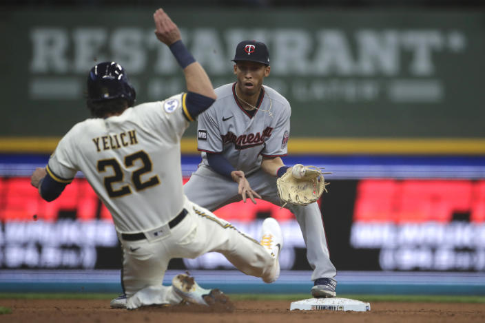 Milwaukee Brewers' Christian Yelich (22) slides in safely at second base as Minnesota Twins' Andrelton Simmons is unable to handle a throw during the fifth inning of an Opening Day baseball game Thursday, April 1, 2021, in Milwaukee. (AP Photo/Aaron Gash)