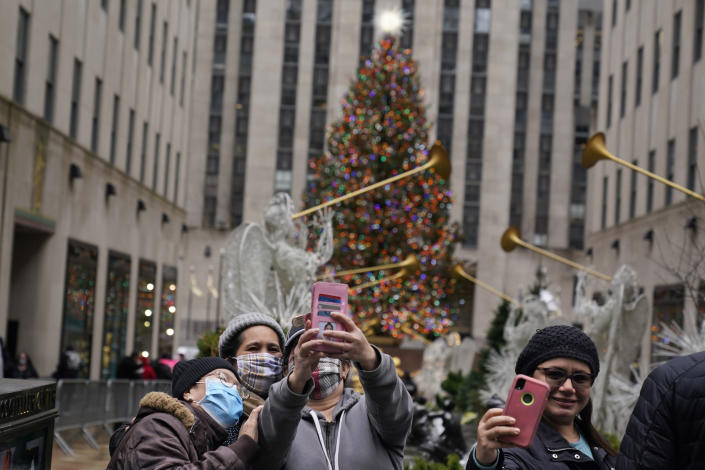 People take pictures of themselves with the Rockefeller Center Christmas tree in New York on Christmas day, Friday, Dec. 25, 2020. The coronavirus upended Christmas traditions, but determination and imagination kept the day special for many. (AP Photo/Seth Wenig)
