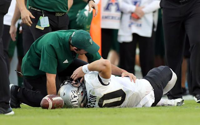 A trainer from South Florida attends to Central Florida quarterback McKenzie Milton after he went down with a knee injury on Friday, Nov. 23, 2018, in Tampa, Fla. (AP)