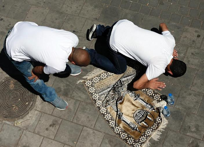 Palestinian Muslim worshippers perform traditional Friday prayers on a street as Israeli police block access to Al-Aqsa Mosque on September 18, 2015 (AFP Photo/Thomas Coex)