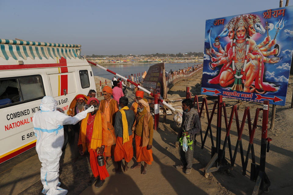 A health worker takes nasal swab samples of Hindu holy men, to test for COVID-19 next to a poster of Hindu God Hanuman during Magh Mela festival, in Prayagraj, India. Wednesday, Feb. 24, 2021. Millions of people have joined a 45-day long Hindu bathing festival in this northern Indian city, where devotees take a holy dip at Sangam, the sacred confluence of the rivers Ganga, Yamuna and the mythical Saraswati. Here, they bathe on certain days considered to be auspicious in the belief that they be cleansed of all sins. (AP Photo/Rajesh Kumar Singh)
