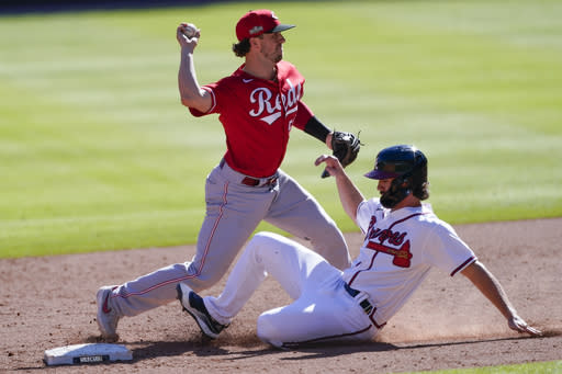 Atlanta Braves' Charlie Culberson is forced out at second base by Cincinnati Reds second baseman Kyle Farmer (52) in 12th inning during Game 1 of a National League wild-card baseball series, Wednesday, Sept. 30, 2020, in Atlanta. (AP Photo/John Bazemore)