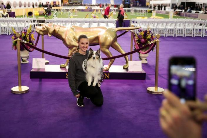 A woman poses for a picture with her dog ahead of the Masters Agility Championship during the Westminster Kennel Club Dog Show in New York