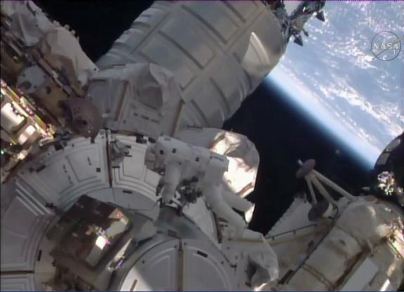 NASA astronauts Scott Kelly and Tim Kopra completed a spacewalk today (Dec. 21), releasing a stuck railcar and moving it to a workstation, where it could be locked down. Here, Kopra works near the recently arrived Cygnus supply craft (top).