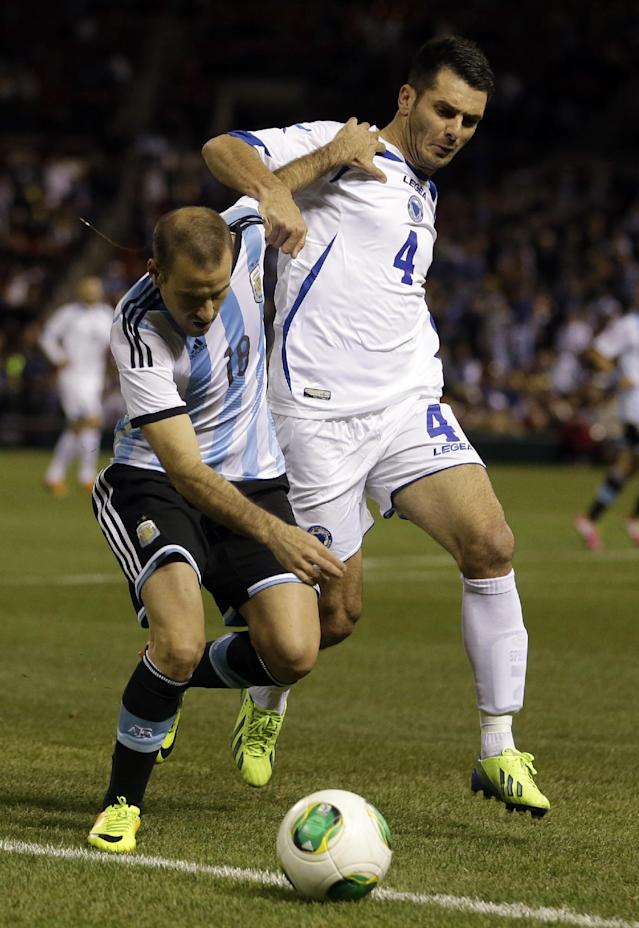 Argentina's Rodrigo Palacio, left, is tackled by Bosnia's Emir Spahic during the first half of an international friendly soccer match Monday, Nov. 18, 2013, in St. Louis. (AP Photo/Jeff Roberson)