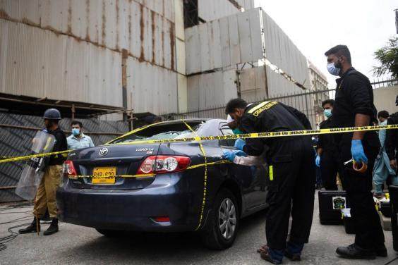 Members of Crime Scene Unit investigate a car used by alleged gunmen at entrance of Stock Exchange building (Getty Images)