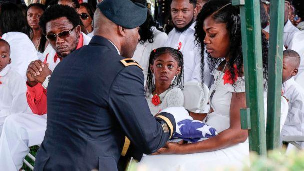 PHOTO: Myeshia Johnson is presented with a folded U.S. flag by a military honor guard member during the burial service for her husband U.S. Army Sgt. La David Johnson at the Memorial Gardens East cemetery, Oct. 21, 2017, in Hollywood, Fla.<p>(Gaston De Cardenas/AFP/Getty Images)