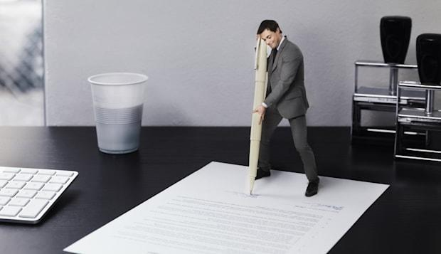 Small businessman signing document on office desk