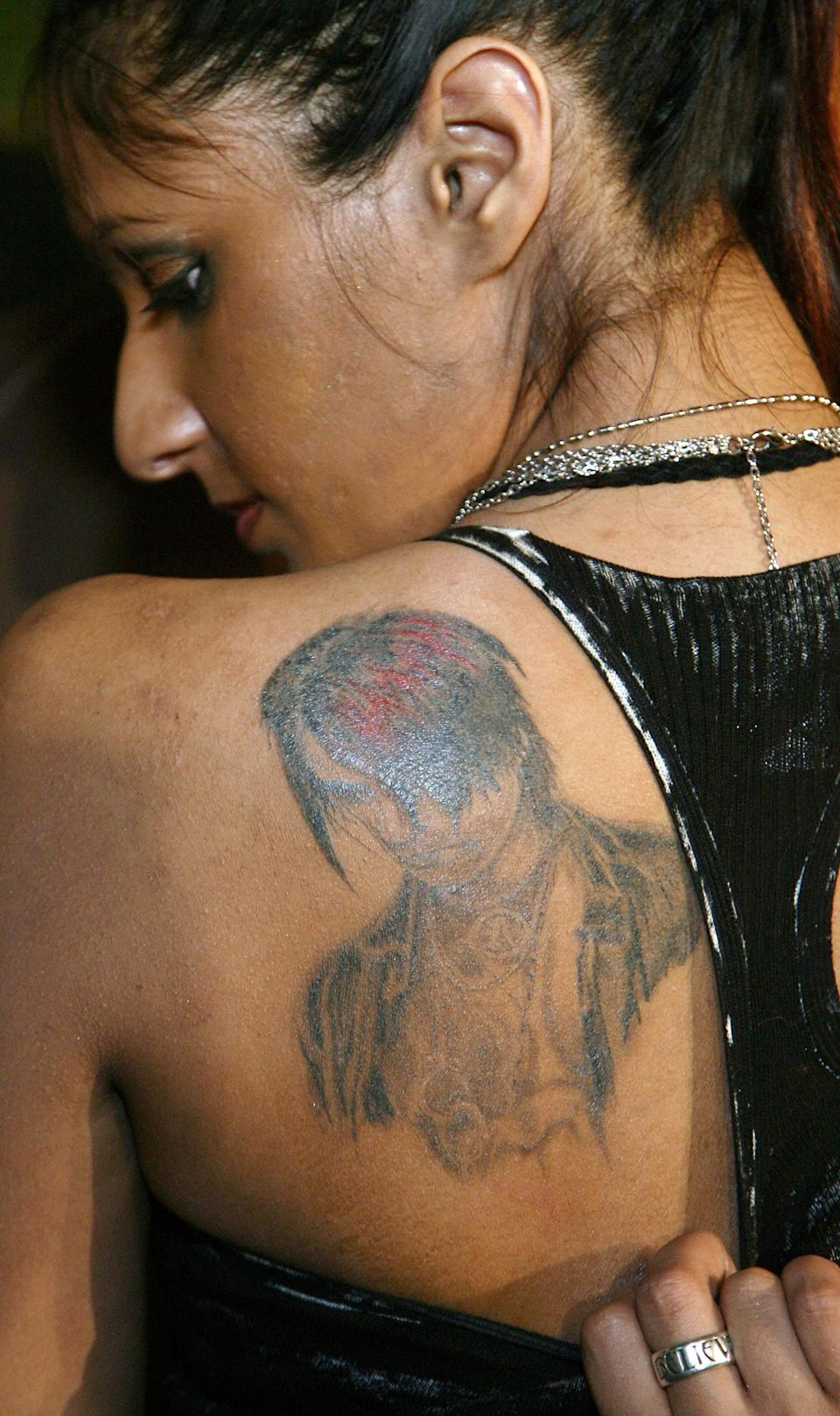 """<div class=""""caption-credit""""> Photo by: Ethan Miller/Getty</div>This woman tattooed your face into her shoulder-blade, Criss Angel. The least you could do is look like you're enjoying yourself."""