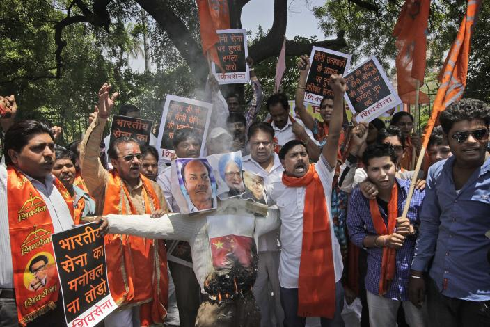 Indian protesters of right wing Shiv Sena party burn an effigy with photographs of India Defense Minister A.K.Antony, left, Prime Minister Manmohan Singh, center and Home Minister Sushil Kumar Shinde during a protest against the alleged incursion by Chinese troops into Indian territory, in New Delhi, India, Wednesday, May 1, 2013. India said Chinese troops crossed the de facto border between the countries and went 10 kilometers (six miles) into Indian territory on April 15. About 50 Chinese soldiers were camping in tents Kashmir's Ladakh region. (AP Photo /Manish Swarup)
